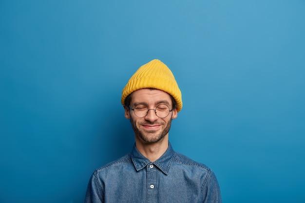 Optimistische caucaisan-man houdt de ogen gesloten, lacht vrolijk, draagt een geel hoofddeksel en een spijkerblouse
