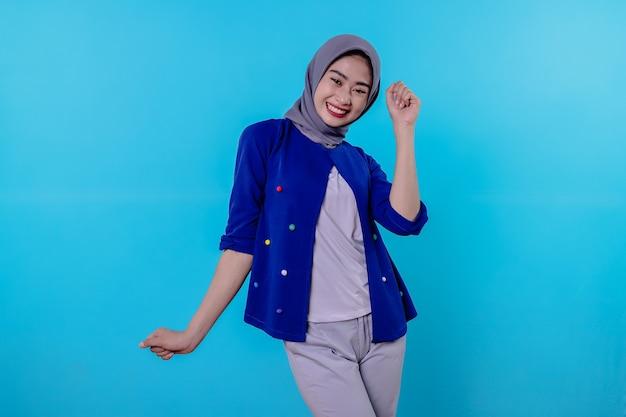 Optimistische charmante aantrekkelijke jonge vrouw met schattige lachende vreugde met mooie witte glimlach op lichtblauwe achtergrond