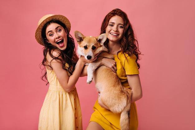 Optimistische dames in gele jurken houden hond vast