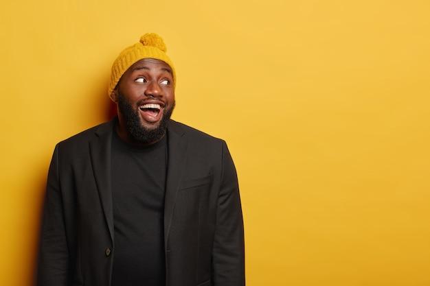 Optimistische donkere man lacht en kijkt weg, draagt warme gebreide muts en zwarte formele kleding, heeft plezier binnen, geïsoleerd op gele achtergrond