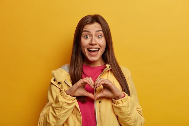 Optimistische donkerharige jonge vrouw vormen hart handteken over borst, drukt liefde, sympathie en genegenheid voor familie uit, kijkt vreugdevol naar de camera