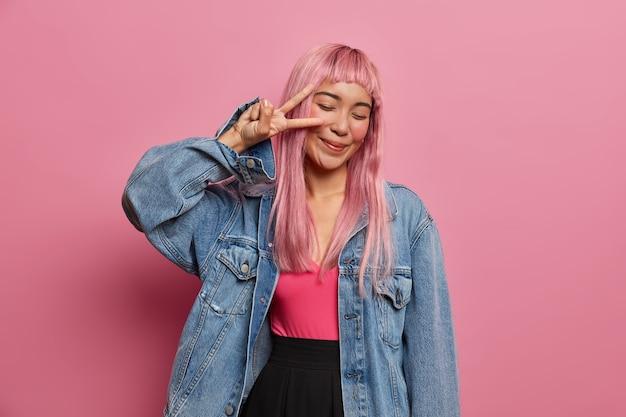 Optimistische energieke langharige vrouw met oosterse uitstraling, roze pruik, maakt vredesgebaar over ogen, glimlacht positief