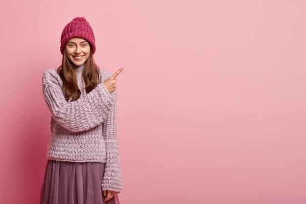 Optimistische europese vrouw wijst rechtsboven weg, draagt modieuze winterkleren, lacht zachtjes, maakt reclame voor iets, geïsoleerd over roze muur. kijk naar de lege ruimte voor promotie