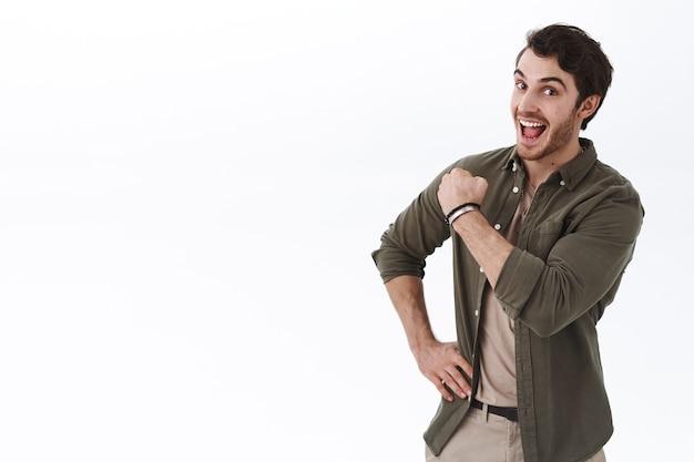 Optimistische, gelukkige en actieve jongeman die aanmoedigt om door te gaan, vuist pompt vrolijk en lacht, waardoor het vertrouwen wordt vergroot