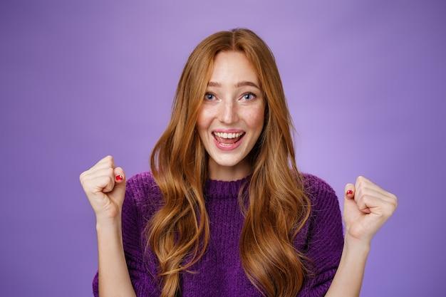 Optimistische, gelukkige jonge aantrekkelijke vrouwelijke student winnende reis rond europees glimlachend in het algemeen van succes en verrukt gebalde vuisten in triomf en vieringsgebaar, blij om de paarse muur te winnen.