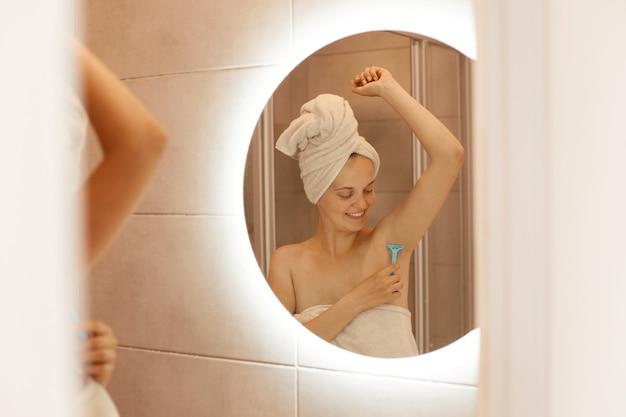 Optimistische gelukkige jonge volwassen vrouw die oksel in de badkamer scheert, naar haar lichaam kijkt, geniet van het ontharingsproces, poseren met blote schouders en gewikkeld in een witte handdoek.