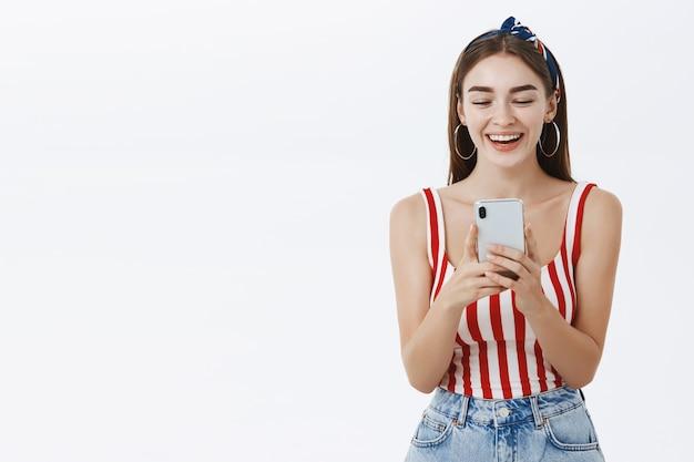 Optimistische gelukkige jonge vrouw die en smartphone lacht gebruikt