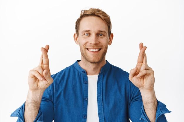 Optimistische gelukkige man kruist zijn vingers voor geluk, glimlacht en ziet er zelfverzekerd uit, verzekerd dat de wens zal uitkomen, wachtend op positieve resultaten, staande over een witte muur