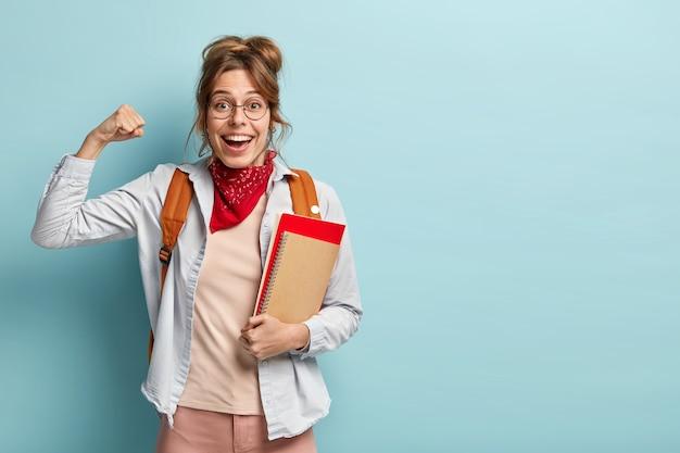 Optimistische gelukkige student met europese uitstraling, gebalde vuisten, toont spieren, viert succesvol afgerond schooljaar