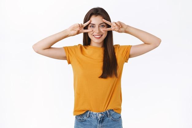 Optimistische, gelukkige vrolijke brunette vrouw in geel t-shirt, vrede of overwinningsteken over ogen tonen, glimlachend uitdrukken van positiviteit en vreugde, genieten van feest, zoals het bijwonen van een geweldig evenement, witte achtergrond