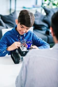 Optimistische ingenieuze jongen die aan zijn robotapparaat werkt terwijl hij geniet van zijn hobby