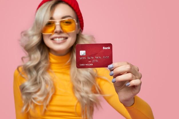 Optimistische jonge hipster-vrouw in gebreide muts en zonnebril die een bankkaart demonstreert terwijl ze reclame maakt voor bankdiensten tegen roze achtergrond