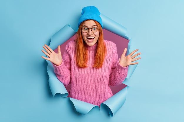 Optimistische jonge roodharige vrouw voelt zich onder de indruk en gefascineerd door iets verheft handpalmen glimlach breed reageert op opwindend nieuws heeft overemotieve blije uitdrukking.