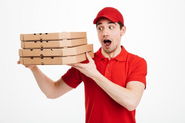 Optimistische kerelhandelaar in rode t-shirt en glb die in de leveringsdienst werken en stapel pizzadozen houden, die over witte ruimte wordt geïsoleerd