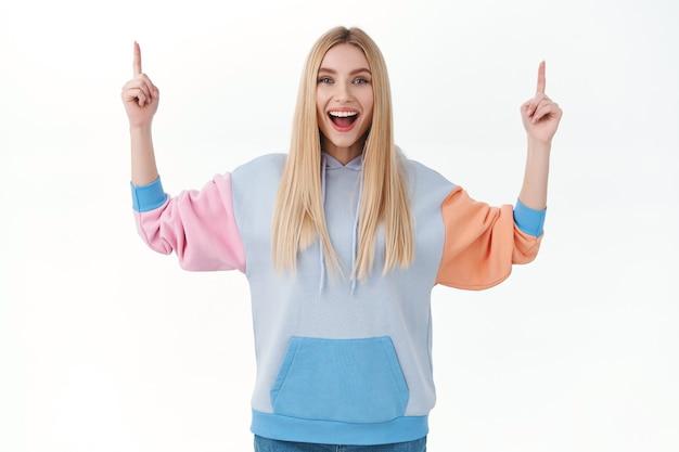 Optimistische, knappe glimlachende gelukkige vrouw met blond lang haar, hoodie, wijzende vingers omhoog en vrolijk grijnzend