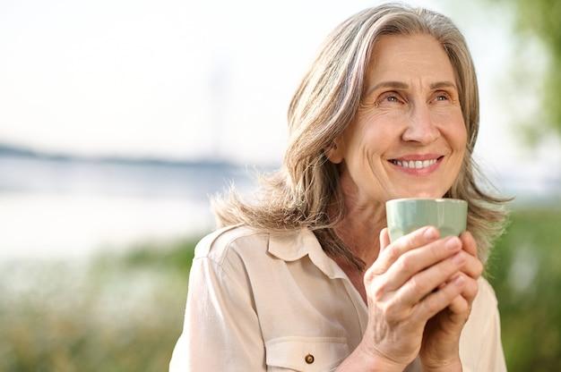 Optimistische lachende vrouw met koffie buitenshuis