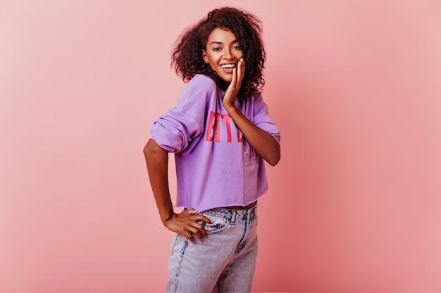 Optimistische leuke vrouw met golvend haar positieve emoties uitdrukken. binnen schot van vrolijke zwarte dame die pret op roze heeft.