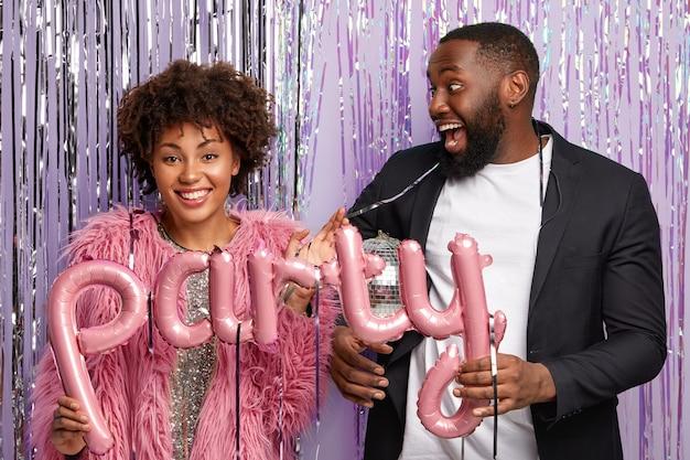 Optimistische man met baard draagt een elegant pak, kijkt vrolijk naar vriendin, viert iets
