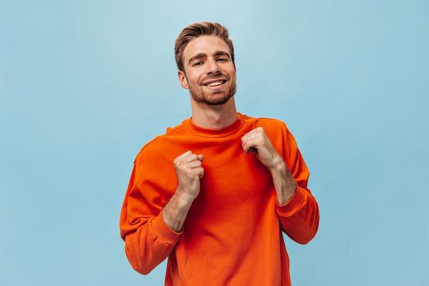 Optimistische man met rode baard en mooie glimlach in oranje fel sweatshirt op zoek naar camera op geïsoleerde blauwe muur