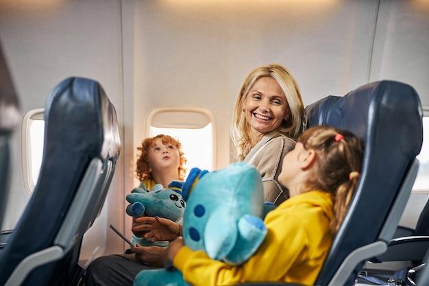 Optimistische moeder kijkt liefdevol naar haar dochter met een speeltje