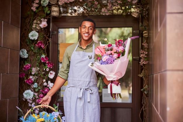 Optimistische multiraciale persoon die uit een winkel komt met een boeket en een mand met heldere bloemen