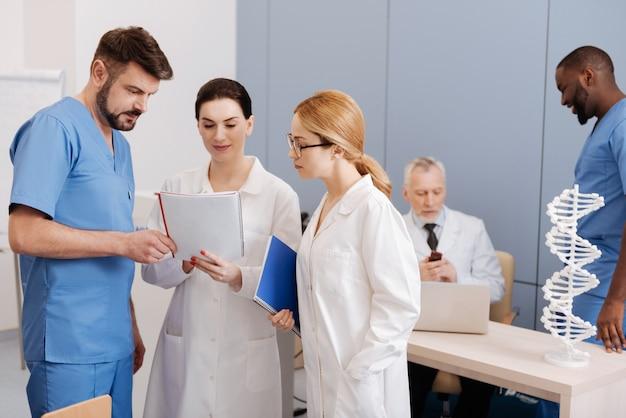 Optimistische nieuwsgierige ervaren beoefenaars die werken en genieten van de conferentie in de kliniek, terwijl ze hun kwalificaties verbeteren en standpunten uitwisselen