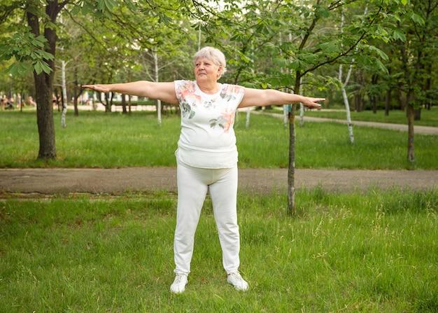 Optimistische oude vrouw die traint voor een gezond leven in de open lucht. rijpe vrouw die yoga beoefent.