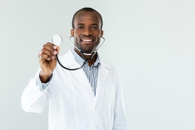 Optimistische rijpe arts die terwijl het houden van een stethoscoop glimlacht