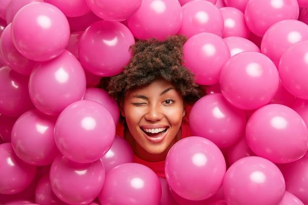 Optimistische verjaardagsvrouw heeft plezier en knipoogt naar het oog glimlacht vreugdevol poseert tegen veel roze ballonnen