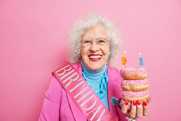 Optimistische volwassen krullende vrouw glimlacht breed geldt lichte make-up houdt donuts met kaarsen viert 91e verjaardag gekleed in feestelijke kleding