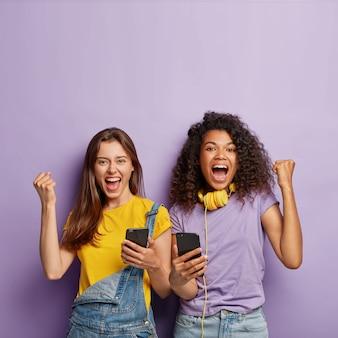 Optimistische vriendinnen poseren met hun telefoons