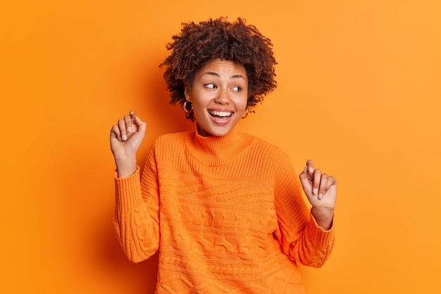 Optimistische vrouw danst met opgeheven armen beweegt zorgeloze glimlach breed gekleed in casual trui geïsoleerd over levendige oranje muur viert prestatie en overwinning geniet van mooie dag