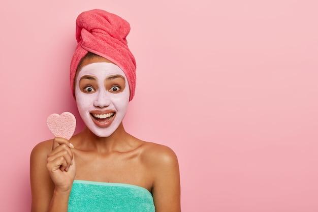 Optimistische vrouw houdt zachte kleine spons voor gezichtsbehandelingen, staat gewikkeld in een handdoek, glimlacht breed, past vers kleimasker toe voor het reinigen van gezicht, gezonde huid. kopieer ruimte voor tekst