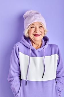 Optimistische vrouw in hoed en kleurrijke pullover in studio, ze is opgewonden