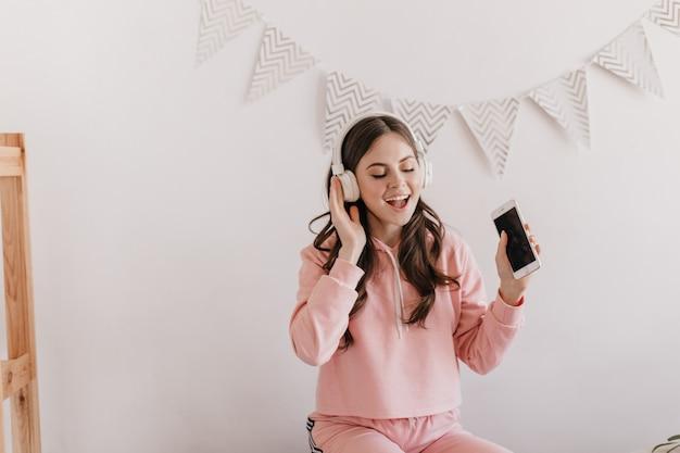 Optimistische vrouw in roze hoodie zingt, luistert naar liedjes in enorme koptelefoons
