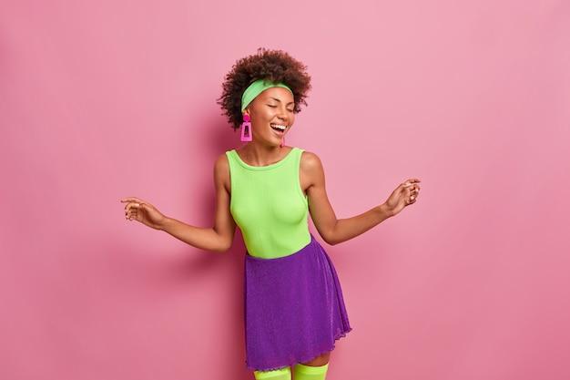 Optimistische vrouw met dolgelukkige uitdrukking, maakt enkele bewegingen, steekt handen op, maakt overwinningsdans, draagt groene en paarse kleding, sluit ogen