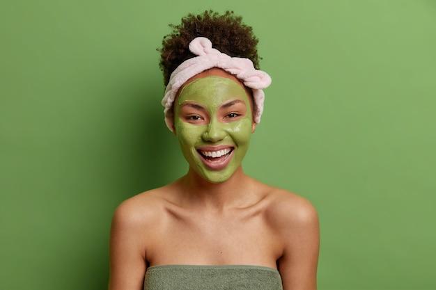 Optimistische vrouw met krullend haar draagt hoofdband past groen voedend masker toe voor huidverzorging na het nemen van douche gewikkeld in handdoek heeft goed verzorgd lichaam geïsoleerd over groene muur