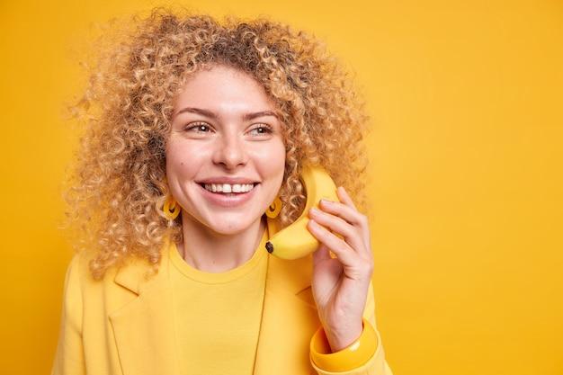 Optimistische vrouw met krullend haar glimlacht aangenaam houdt banaan in de buurt van oor alsof telefoongesprek wegkijkt met dromerige uitdrukking geïsoleerd over gele muurkopie ruimte.