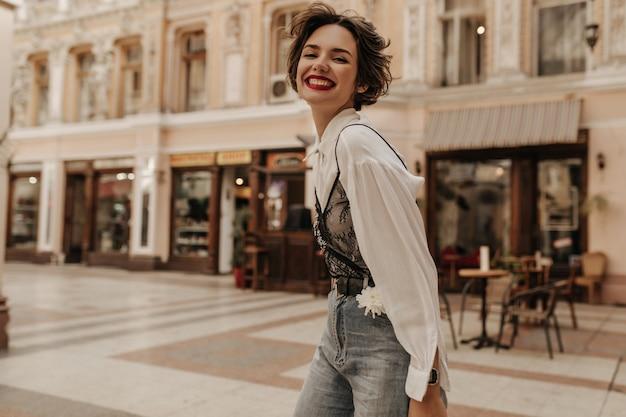 Optimistische vrouw met krullend haar in spijkerbroek oprecht glimlachen in de stad. stoere dame in lichte blouse met zwart kant op straat.