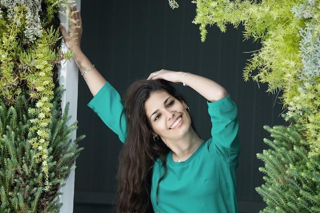 Optimistische vrouwelijke ontspannen op groen balkon