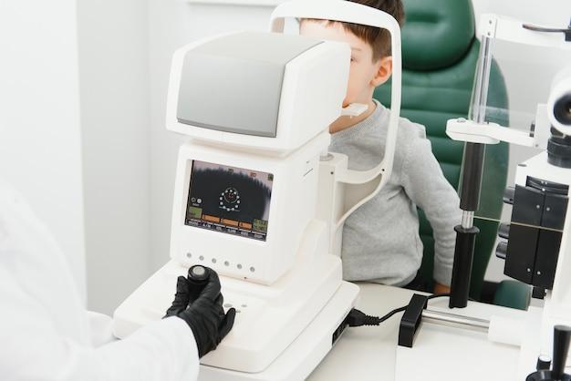 Optometrie concept. vrouwelijke optometrist opticien arts onderzoekt gezichtsvermogen van kind jongen in oog oftalmologische kliniek