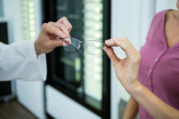 Optometrist die bril geeft aan klant in optische winkel