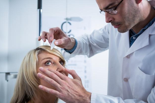 Optometrist die druppels in de ogen van de patiënt brengt