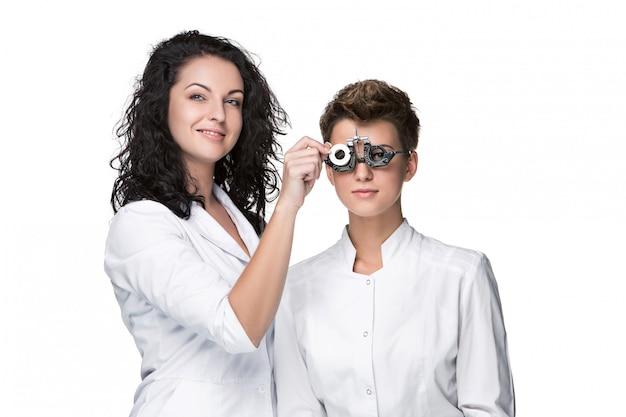 Optometrist die een bril van de oogtest houdt en aan jong vrouwenonderzoek geeft