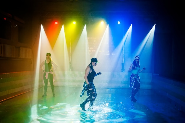 Optreden op het water van een dansgroep tegen de achtergrond van clublicht.