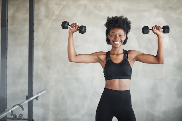 Opvatting van kracht. studio shot van jonge vrouw die voor grijze achtergrond staat met halters in handen
