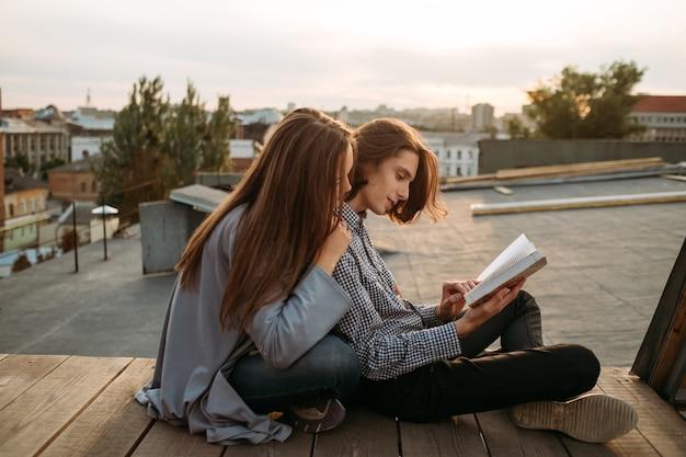 Opvoeden en studeren. ontspannen manier om nieuwe informatie te leren. studenten lezen een boek op een dak
