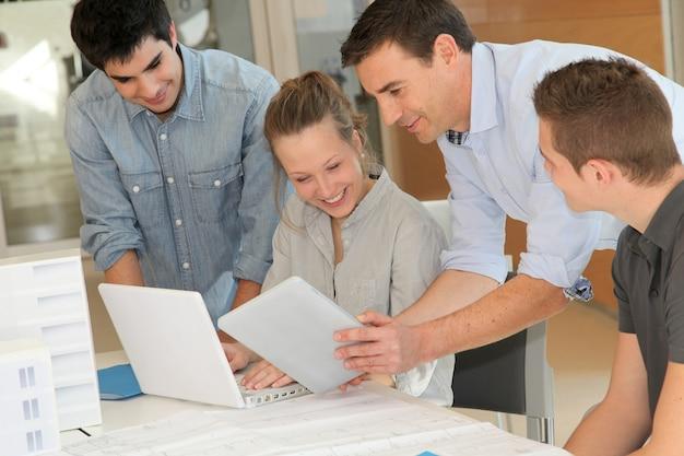 Opvoeder met studenten in architectuur die aan elektronische tablet werken