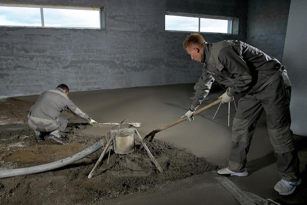 Opvullen van de vloer met beton, dekvloer en egalisatievloer door bouwvakkers