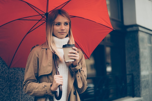 Opwarmen met hete koffie. aantrekkelijke jonge vrouw met paraplu en koffiekopje terwijl ze op straat staat